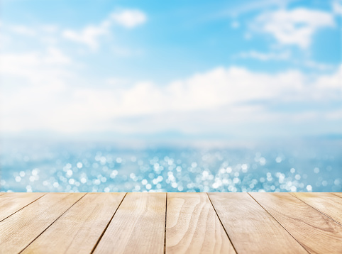 istock Wooden table top on blue sea and white sand beach 530427836