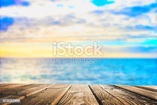 istock Wooden table top on blue sea and white sand beach 925083988