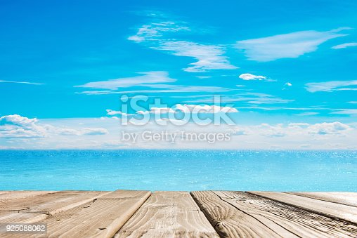 istock Wooden table top on blue sea and white sand beach 925088062