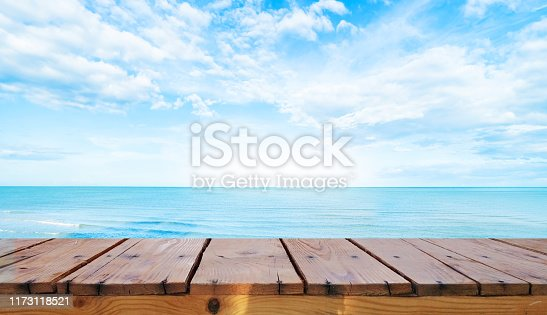 530427836istockphoto Wooden table top on blue sea 1173118521