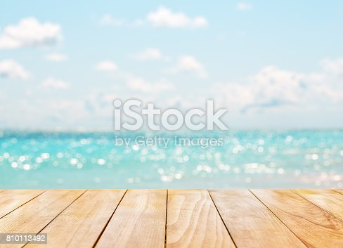 istock Wooden table top on blue sea 810113492