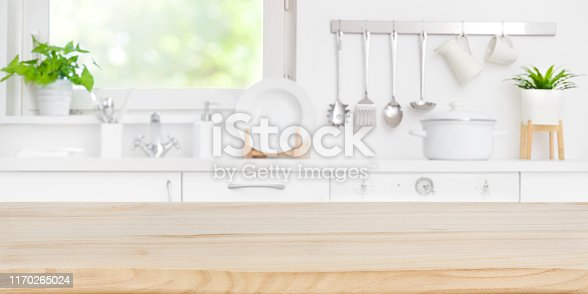 Wooden table top on blur kitchen room and window background