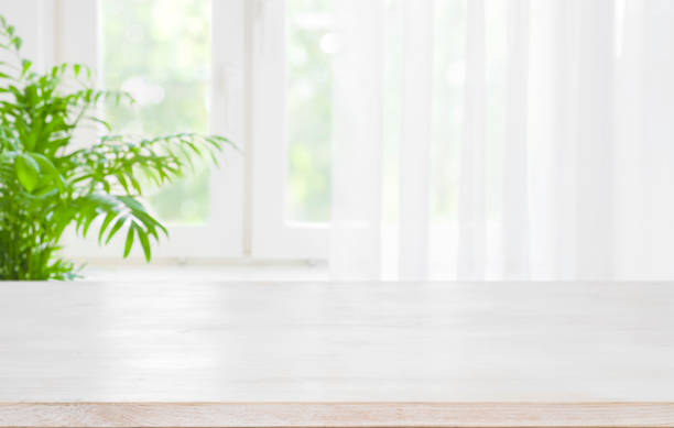 木桌頂部在半窗簾視窗的模糊背景 - 明亮 個照片及圖片檔