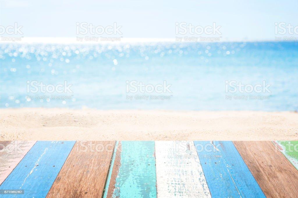 木桌上模糊的海灘背景圖像檔