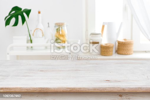 697868238 istock photo Wooden table top on blurred kitchen window and shelves background 1092062952