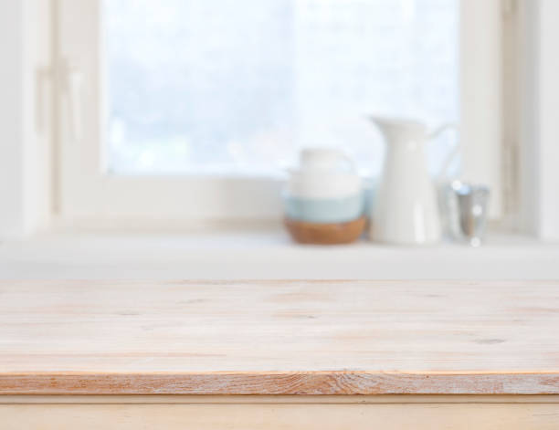 Wooden table top on blurred kitchen window background – zdjęcie