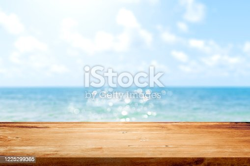 istock Wooden table top on blurred summer blue sea and sky background. Copy space for your display or montage product design. 1225299365