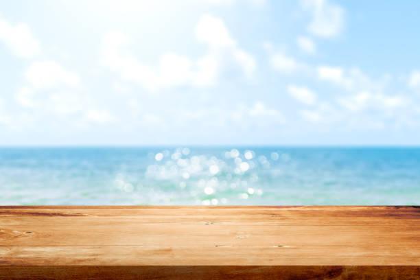 tablero de mesa de madera sobre el mar azul de verano borroso y fondo del cielo. copie espacio para el diseño del producto de visualización o montaje. - playa fotografías e imágenes de stock
