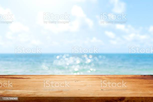 Photo of Wooden table top on blurred summer blue sea and sky background. Copy space for your display or montage product design.