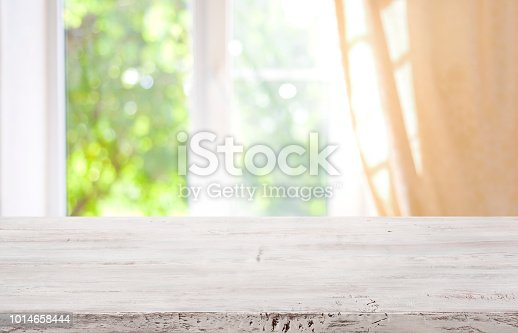885452818istockphoto Wooden table top on blurred window background for product display 1014658444