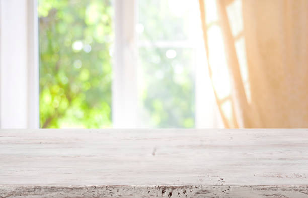 Wooden table top on blurred window background for product display stock photo