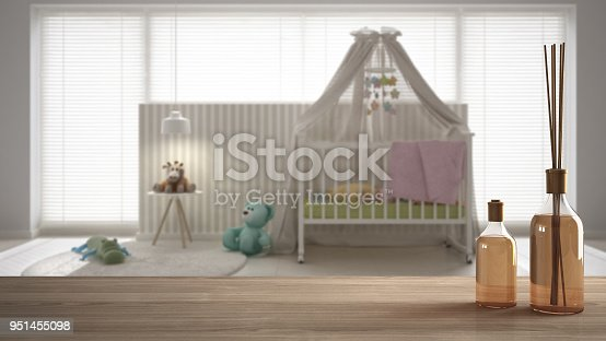 istock Wooden table top or shelf with aromatic sticks bottles over blurred child's room with cradle, carpet and bed side table, white architecture interior design 951455098