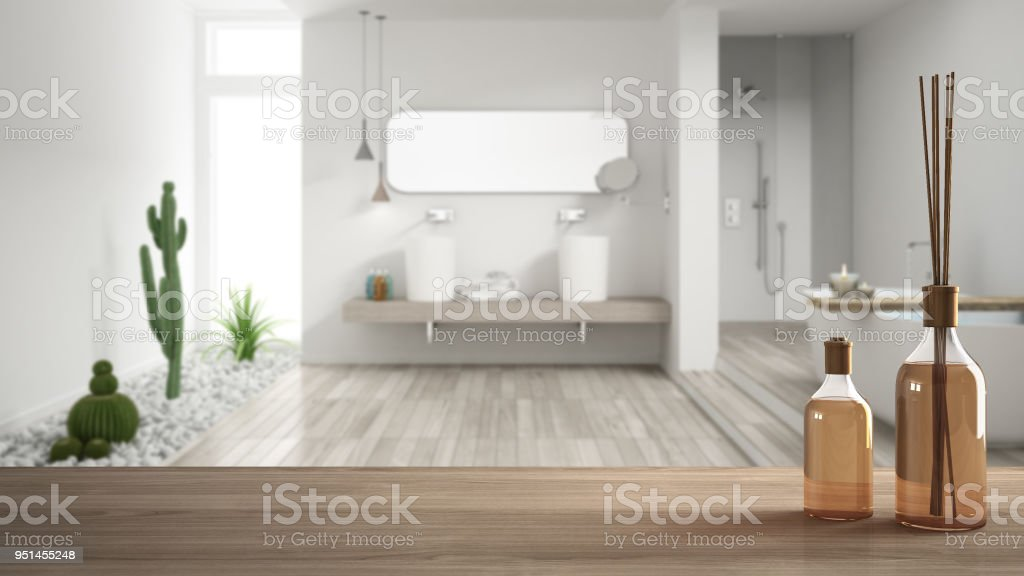 Wooden table top or shelf with aromatic sticks bottles over blurred modern bathroom with garden, white architecture interior design stock photo