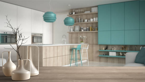Wooden table top or shelf with minimalistic modern vases over blurred minimalistic turquoise kitchen, white interior design stock photo