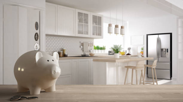 Wooden table top or shelf with white piggy bank with coins, scandinavian white and wooden kitchen, expensive home interior design, renovation restructuring concept architecture stock photo
