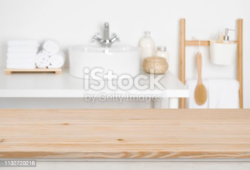 819534860istockphoto Wooden table top over blurred bathroom interior as the background 1132720216