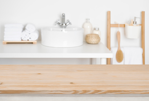 819534860 istock photo Wooden table top over blurred bathroom interior as the background 1132720216
