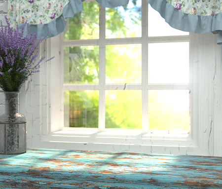 A wooden table top with a blue color and vase of lavender in front of blurred background.