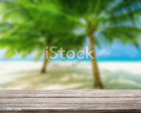 istock wooden table top with blur ocean background summer concept - Image 1139972206