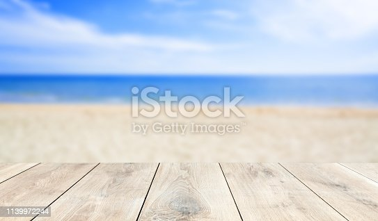 istock wooden table top with blur ocean background summer concept - Image 1139972244