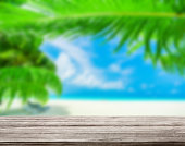 istock wooden table top with blur ocean background summer concept - Image 1139972264