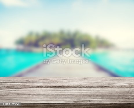 istock wooden table top with blur ocean background summer concept - Image 1139972270