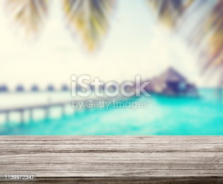 istock wooden table top with blur ocean background summer concept - Image 1139972347