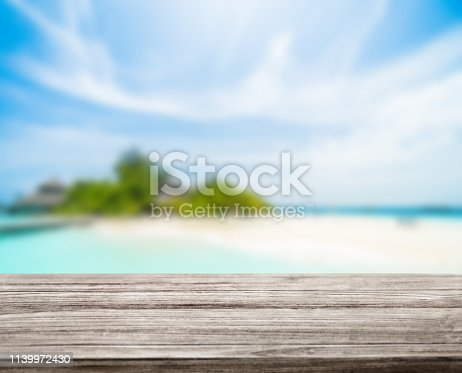 istock wooden table top with blur ocean background summer concept - Image 1139972430