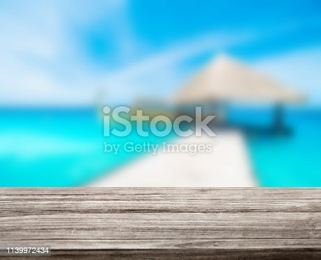 istock wooden table top with blur ocean background summer concept - Image 1139972434