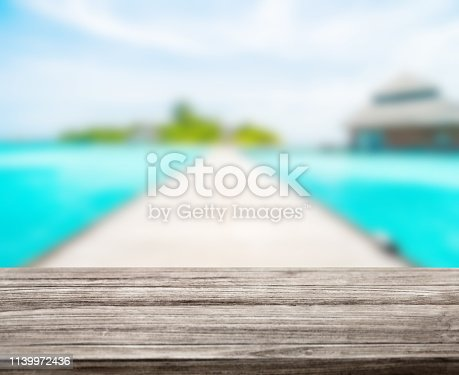 istock wooden table top with blur ocean background summer concept - Image 1139972436