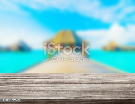 istock wooden table top with blur ocean background summer concept - Image 1139972529