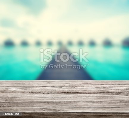 istock wooden table top with blur ocean background summer concept - Image 1139972531