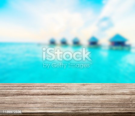 istock wooden table top with blur ocean background summer concept - Image 1139972536