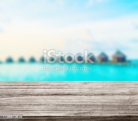 istock wooden table top with blur ocean background summer concept - Image 1139972614