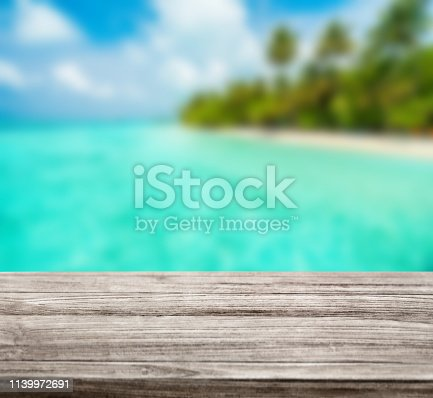 530427836 istock photo wooden table top with blur ocean background summer concept - Image 1139972691