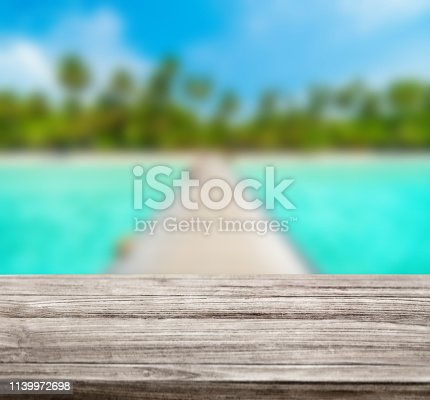 istock wooden table top with blur ocean background summer concept - Image 1139972698
