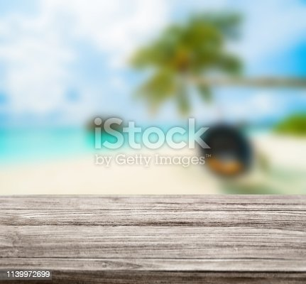 istock wooden table top with blur ocean background summer concept - Image 1139972699