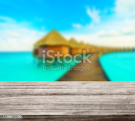 istock wooden table top with blur ocean background summer concept - Image 1139972700