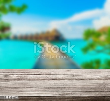 istock wooden table top with blur ocean background summer concept - Image 1139972740