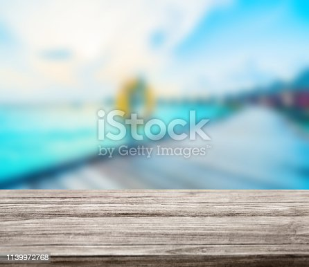 istock wooden table top with blur ocean background summer concept - Image 1139972768