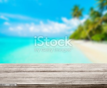 istock wooden table top with blur ocean background summer concept - Image 1139972778