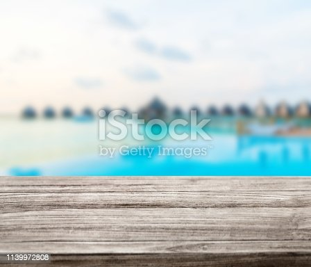 530427836istockphoto wooden table top with blur ocean background summer concept - Image 1139972808