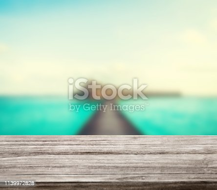 istock wooden table top with blur ocean background summer concept - Image 1139972828