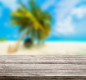 istock wooden table top with blur ocean background summer concept - Image 1139972875