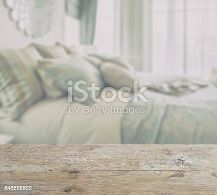 istock wooden table top with blur of bedroom interior with pillows 545558522