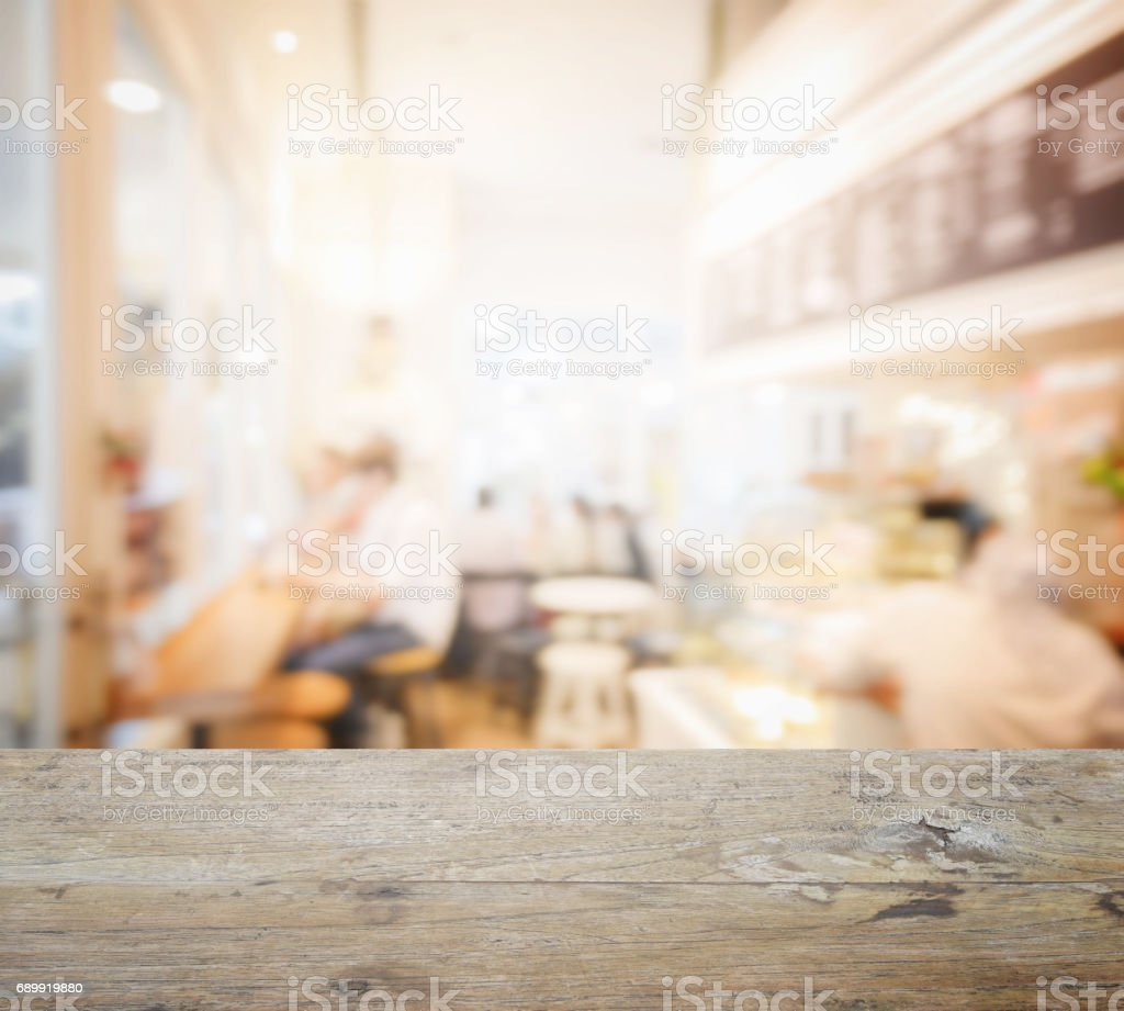 wooden table top with blur of coffee shop interior as background stock photo