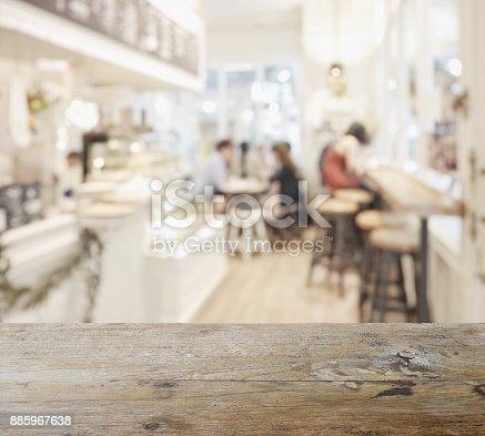 885959540istockphoto wooden table top with blur of coffee shop interior as background 885967638