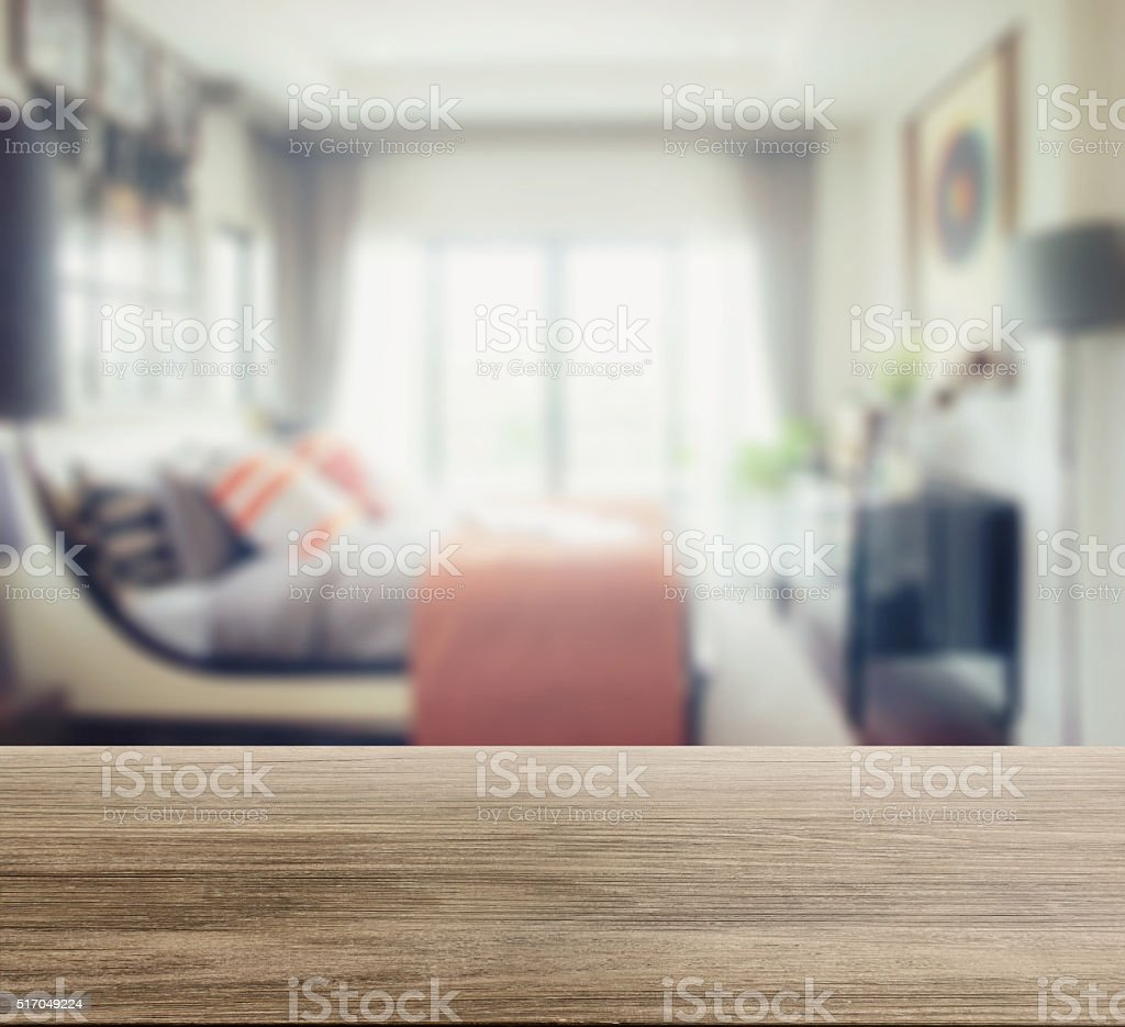 wooden table top with blur of modern bedroom interior stock photo