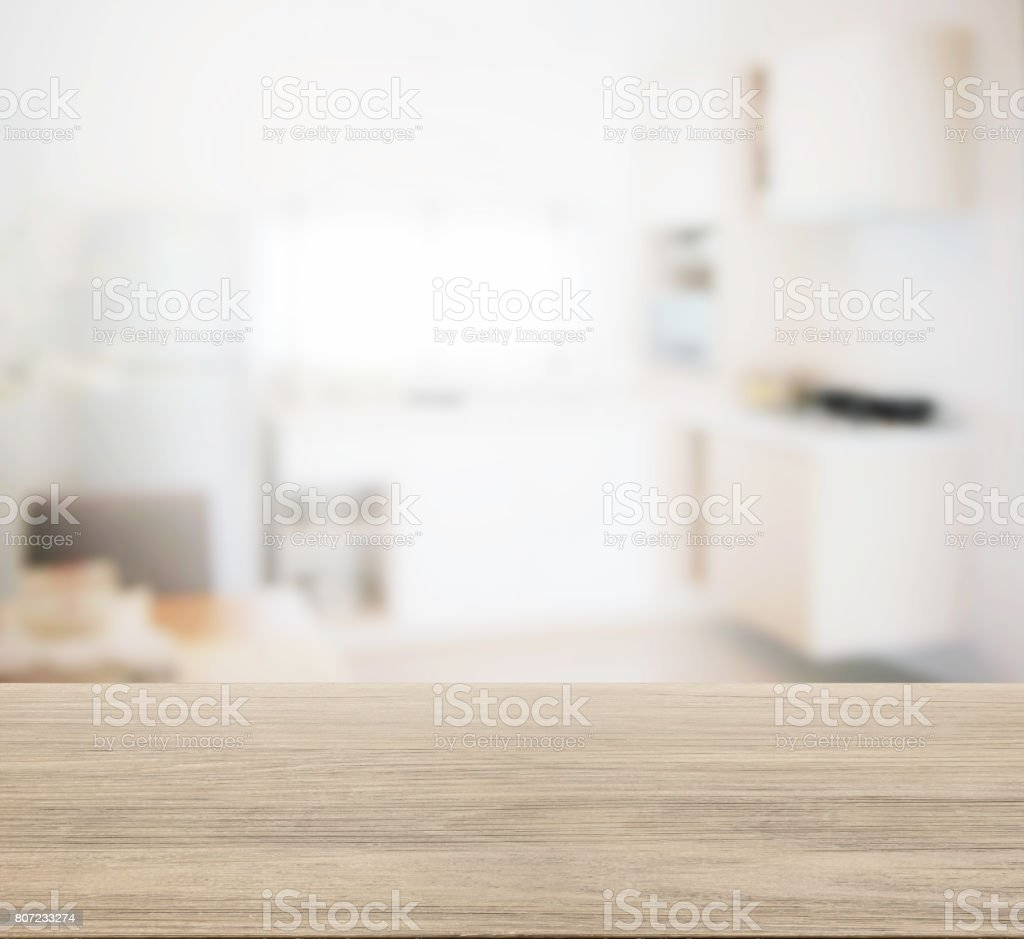 wooden table top with blur of modern kitchen interior for background stock photo