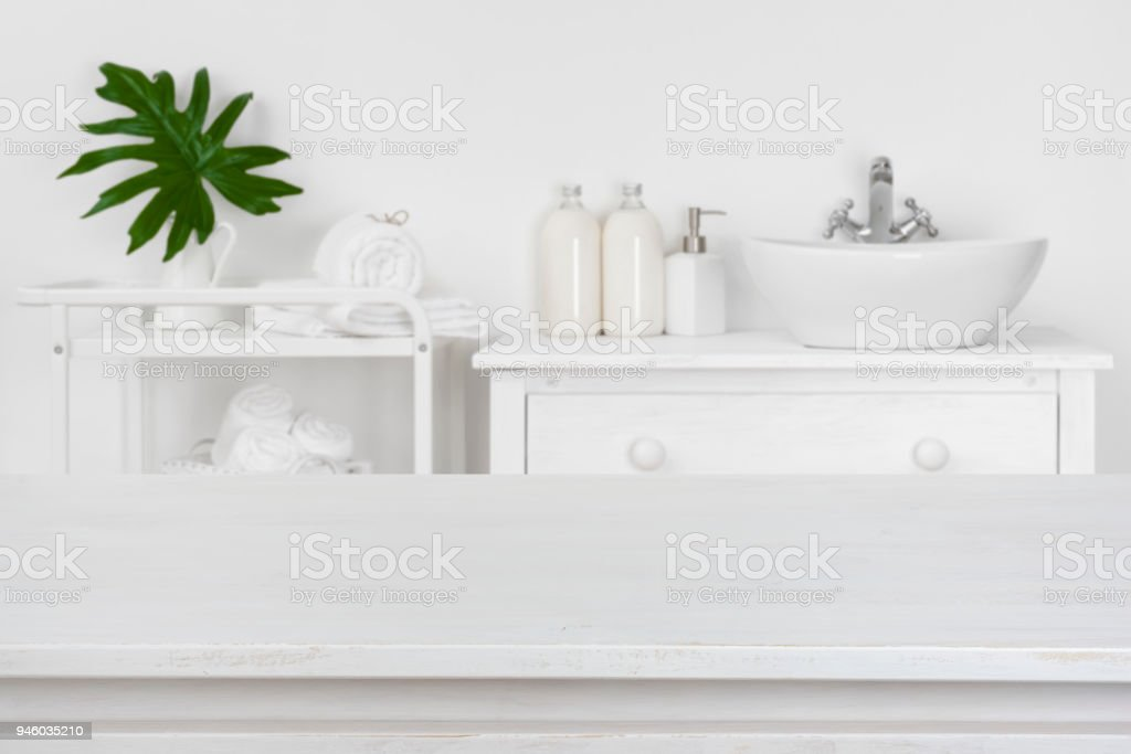 Wooden table top with blurred bathroom interior for product display stock photo